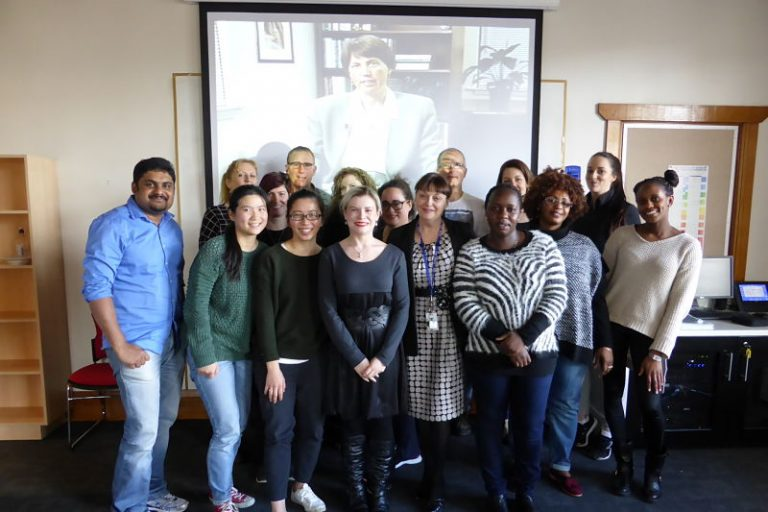 university of tasmania's senior lecturer christine handley with her postgraduate nursing students and a large photo of christine padesky as the backdrop