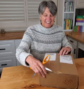 padesky sitting at desk unboxing the 2nd edition of the clinicians guide to cbt